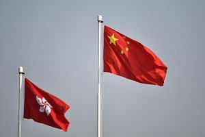 The Chinese national flag (right) flutters alongside the Hong Kong flag during a ceremony in Hong Kong, on Oct 1, 2019.