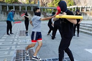 Masked participants spar with foam sticks during a self-defence class organised by a student union at the Chinese University of Hong Kong, on Oct 15, 2019.