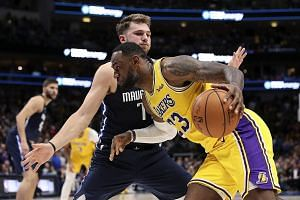 Los Angeles Lakers' LeBron James finding the Dallas Mavericks' Luka Doncic a tough obstacle to get past in the overtime period. The Lakers won 119-110.