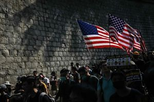In a photo taken on Sept 8, 2019, protesters carry US national flags during a march from Chater Garden to the US Consulate in Hong Kong.