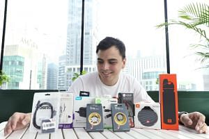 Mr Kenneth Koh, 25, poses for a picture with some of his past purchases at his office at Keppel Towers 2, on Nov 7, 2019.