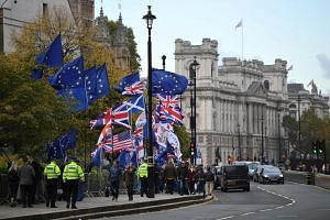 Demonstrators hold EU and UK flags as they walk near the Houses of Parliament in central London, on Oct 29, 2019.
