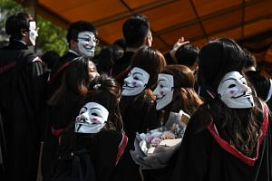 University students wear Guy Fawkes masks during an anti-government protest at their graduation ceremony at the Chinese University of Hong Kong on Nov 7, 2019.