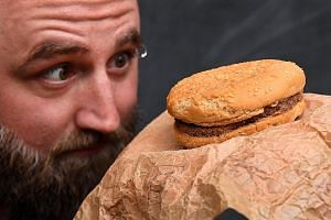 Mr Casey Dean with the McDonald's Quarter Pounder with cheese that he said was bought in 1995. Though the burger has shrunk a little from its original size, its shape remains intact, there are no signs of mould and it does not smell. PHOTO: AGENCE FR