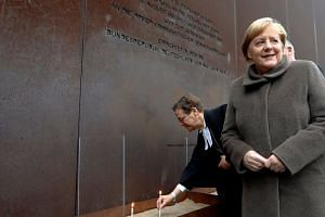 German Chancellor Angela Merkel attends a lighting of candles ceremony at the memorial of the divided city in Berlin.