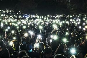 Activists light up their mobile phones as they take part in a memorial rally at Tamar Park to mourn a university student in Hong Kong on Nov 9, 2019.