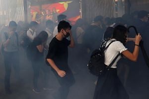 In a photo taken on Nov 11, 2019, office workers run away from tear gas as they attend a flash mob anti-government protest at the financial Central district in Hong Kong.