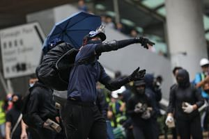 A pro-democracy protester throwing stones to block a road during a lunchtime flash mob in Central, Hong Kong, on Nov 12, 2019.