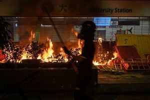 Protesters burn the entrance gate of a metro station after the clashes with protesters at the Chinese University of Hong Kong, in Hong Kong on Nov 13, 2019.