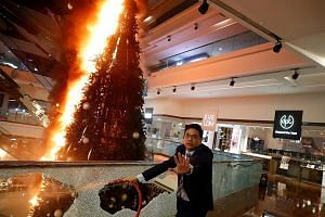 """A man trying to extinguish a burning Christmas tree at Festival Walk mall in Kowloon Tong, Hong Kong, on Tuesday. The shopping centre, owned by Singapore-listed Mapletree North Asia Commercial Trust, suffered """"extensive damage"""" caused by protesters o"""