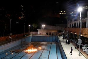 Protesters practise throwing molotov cocktails into a swimming pool at the Polytechnic University in Hong Kong on Nov 14, 2019.