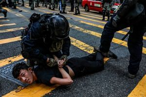 Police detain a demonstrator during a flash mob protest in the Central district in Hong Kong on Nov 13, 2019.