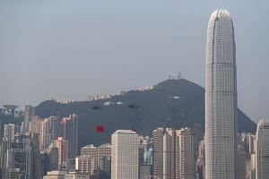 Helicopters on Oct 1 carrying China's national flag and Hong Kong's flag flying past the skyline of Victoria Harbour in Hong Kong on China's National Day. A push in the US Congress for legislation to support pro-democracy protests in Hong Kong and pr