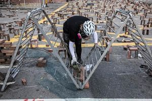A protester pouring cement onto a makeshift barricade on a street outside the Hong Kong Polytechnic University on Nov 15, 2019.