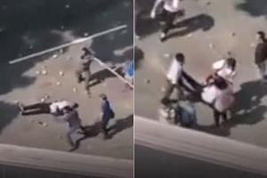 Video footage shows the man lying on the ground unconscious while volleys of bricks are being thrown by the protesters and the group trying to clear the roadblock.