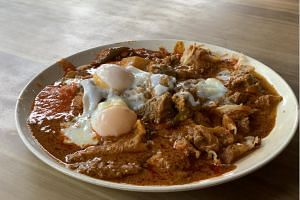 The R.K. Special at R.K. Eating House comes with two pieces of crispy plain prata drenched in mutton curry and topped with two wobbly soft-boiled eggs.