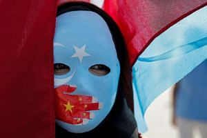 An ethnic Uighur demonstrator wears a mask as she attends a protest against China in Turkey.