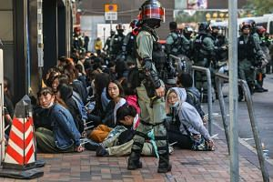 People are detained by police near the Hong Kong Polytechnic University in Hong Kong on Nov 18, 2019.