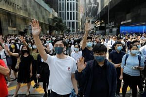 Demonstrators raise their hands as they take to the streets during a protest at the Central District in Hong Kong, on Nov 15, 2019.