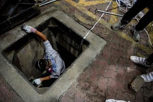 A protester climbs down a sewer entrance at the Hong Kong Polytechnic University on Nov 19, 2019.