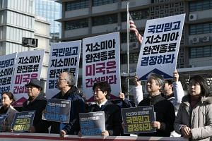 "South Korean protesters hold placards reading ""complete end to GSOMIA, the US should stop interfering"" during a rally in front of the US embassy in Seoul on Nov 22, 2019."