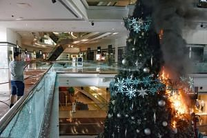 In a photo from Nov 13, 2019,  a person tries to extinguish a burning Christmas tree after protesters set fire to it at Festival Walk shopping mall in Hong Kong.