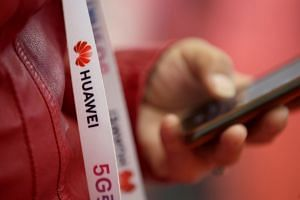 An attendee wears a badge strip with the logo of Huawei and a sign for 5G at the World 5G Exhibition in Beijing, China.