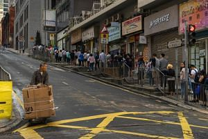 People queueing outside a polling station to cast their vote in the Hong Kong district council election, on Nov 24, 2019.