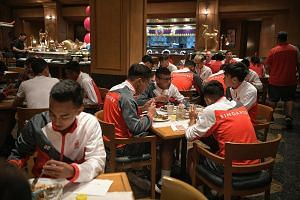 Above: The Singapore national football team having dinner with a wider variety of halal food yesterday at the Century Park Hotel's restaurant. Left: Last-minute renovation work being carried out yesterday at the Rizal Memorial Stadium, where football
