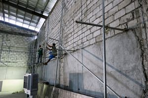 Construction workers stand on scaffolding inside an unfinished structure at the SEA Games, in Rizal Memorial Stadium, Manila, Philippines, on Nov 26, 2019.