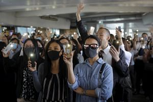 Office workers and pro-democracy protesters flash their mobile phone lights and hold up their hands to represent their five demands wanted from the government as protests continue in Central district of Hong Kong, on Nov 27, 2019.