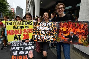 Students hold placards during a rally calling for action on climate change in front of the Liberal Party headquarters in Sydney on Nov 29, 2019.