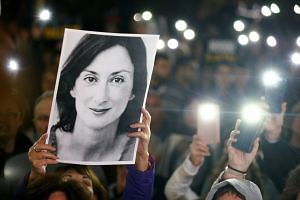 People hold up a photo of murdered journalist Daphne Caruana Galizia as they call for the resignation of Maltese Prime Minister Joseph Muscat at the Great Siege Square in Valletta, Malta on Nov 20, 2019.