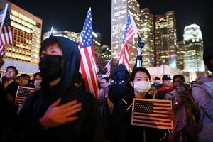Pro-democracy protesters hold US national flags during a Thanksgiving rally in Edinburgh Place, Hong Kong, on Nov 28, 2019.