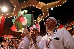 Umno and PAS members during their unity gathering in Kuala Lumpur in September. The two Malay-Muslim parties are working on a mechanism to ensure only a BN or a PAS candidate will face off against PH in an electoral fight - a tactic that led to succe