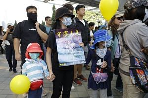 "A masked woman and children hold balloons and a placard which reads ""Guard the Future"" during a ""No Tear Gas"" rally march in Hong Kong, on Dec 1, 2019."
