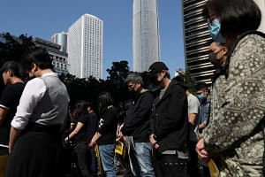 Anti-government demonstrators stand still during a moment of silence as people gather for a lunchtime protest at Chater Garden in Hong Kong, on Dec 2, 2019.