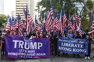 Pro-democracy protesters holding US flags marching in Hong Kong on Dec 1, 2019. China said it has suspended the review of requests by US military ships and aircraft to visit Hong Kong.