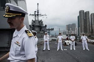 This photo taken on April 20, 2019, shows crew members standing on the deck of the USS Blue Ridge during a port call in Hong Kong.