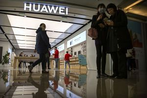 In a photo taken on Nov 20, 2019, people stand outside of a Huawei store at a shopping mall in Beijing.