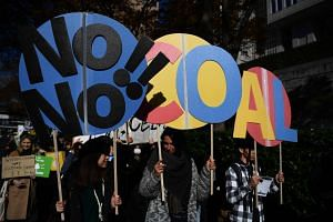 In a photo taken on Nov 29, 2019, participants hold up placards as they take part in a call for action on climate change with a couple of hundred people during a march in Tokyo.