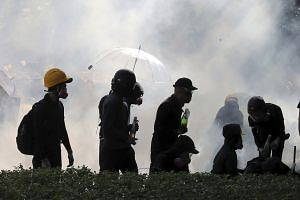 In a photo from Nov 17, 2019, pro-democracy protestors react as police fire tear gas at Hong Kong Polytechnic University in Hong Kong.