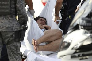 An unidentified male is taken away on a stretcher outside the main gate at Joint Base Pearl Harbor-Hickam.
