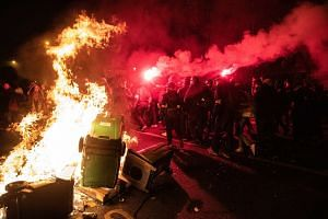 Demonstrators light a fire and flares while protesting during a national strike in Paris on Dec 5, 2019.