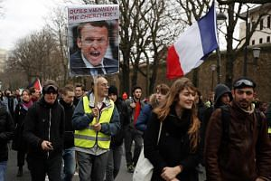 In a photo taken on Dec 7,  yellow vests protesters hold a portrait of French President Macron and a French flag march in Paris.