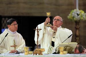 A photo taken on Jan 16, 2015, shows Pope Francis, with Manila Cardinal Luis Antonio Tagle, holding a Mass at the Manila Cathedral.