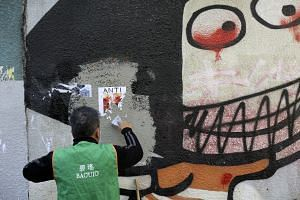 A worker cleans up a vandalized wall in Hong Kong on Dec 9, 2019. The city witnessed its largest mass rally in months on Dec 8, with organisers estimating some 800,000 people participating.
