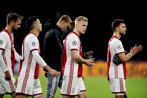 Ajax players react after the match.