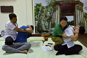 A Thai instructor (left) trains his student from Hong Kong (right) at the Wat Po Thai traditional massage school in Bangkok.