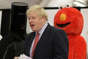 British Prime Minister and Conservative Party leader Boris Johnson is flanked by fellow Uxbridge candidates Lord Buckethead (left) and Bobby Elmo Smith (right) in London on Dec 13, 2019.